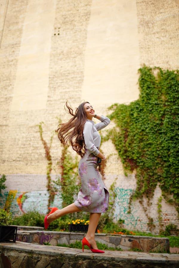 Muchacha morena elegante y muy hermosa en el traje gris que salta para arriba imagenes de archivo