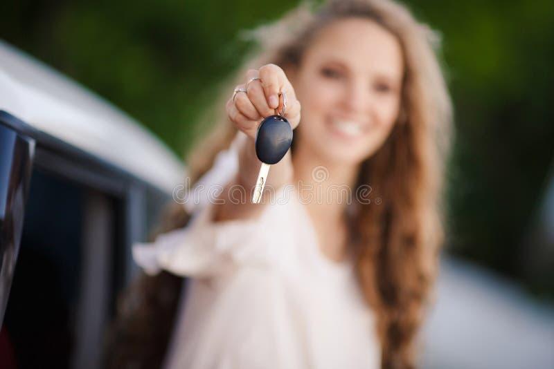 Muchacha morena embarazada y su coche rojo fotografía de archivo