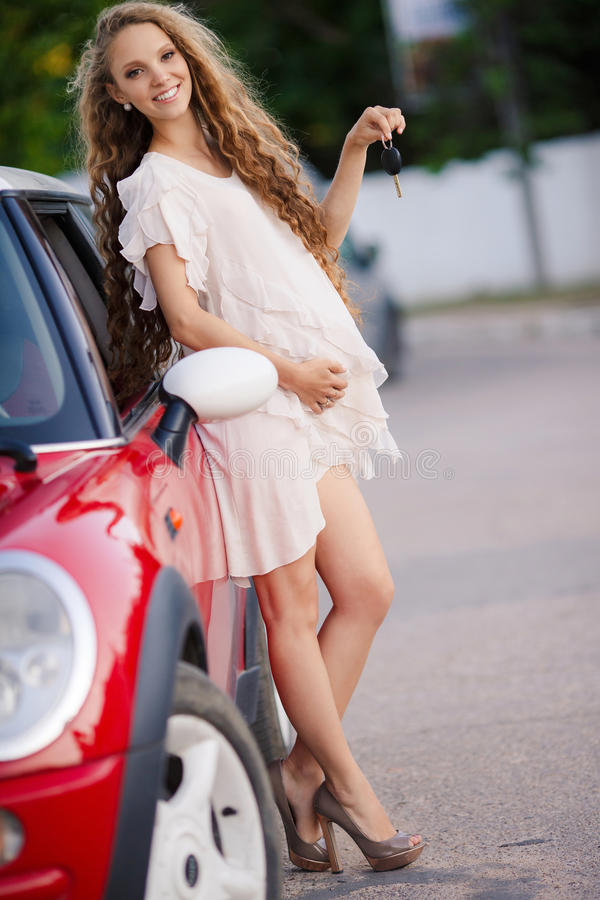 Muchacha morena embarazada y su coche rojo foto de archivo libre de regalías