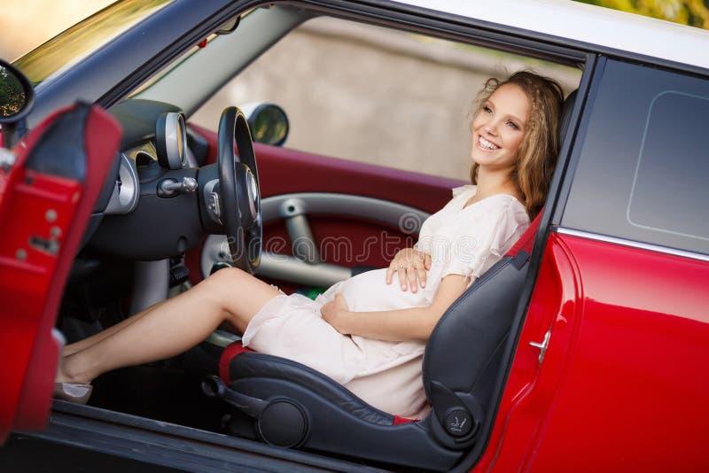 Muchacha morena embarazada y su coche rojo imagen de archivo libre de regalías