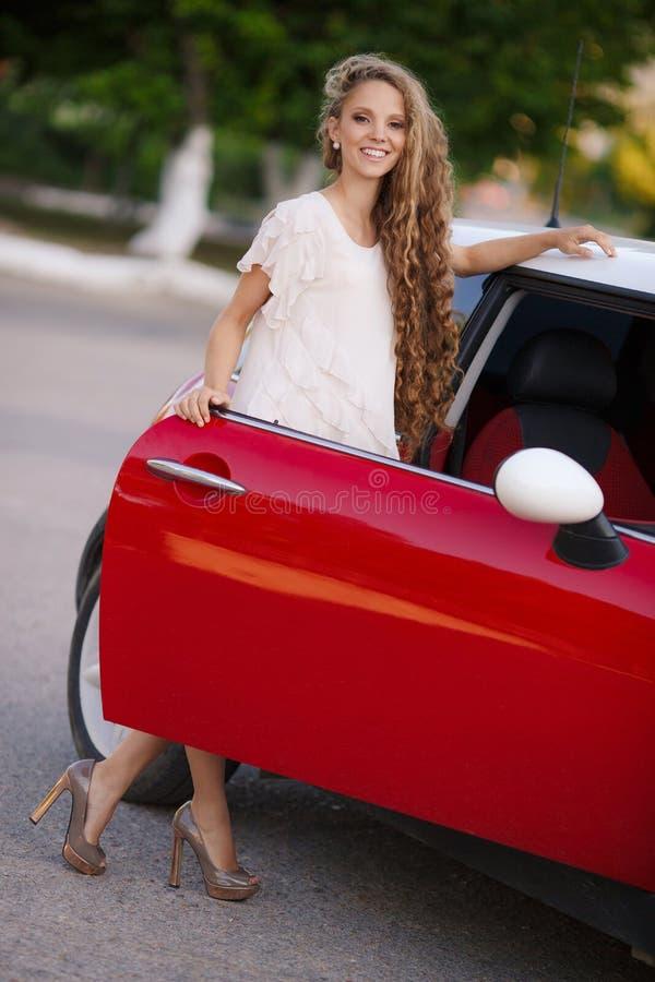 Muchacha morena embarazada y su coche rojo imagen de archivo