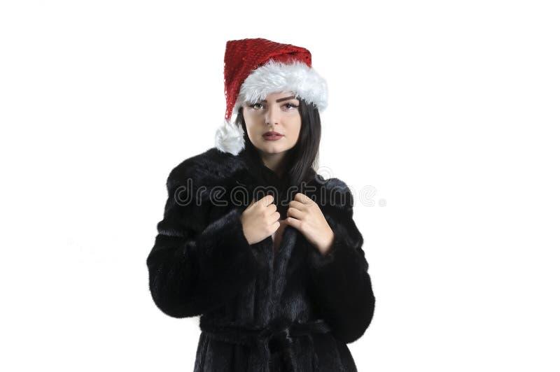 Muchacha morena en abrigo de pieles negro en el sombrero de santa en el retrato aislado del fondo foto de archivo