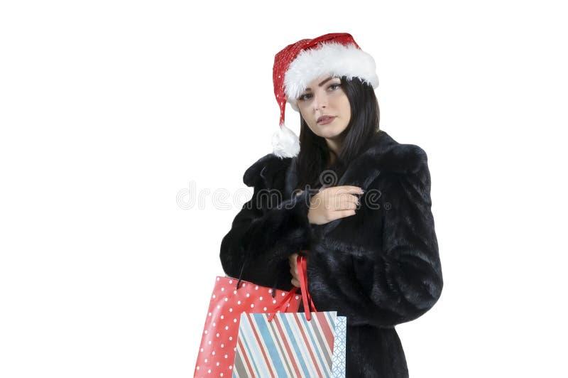 Muchacha morena en abrigo de pieles negro en los panieres atractivos de santa en el fondo aislado, compras de la Navidad, venta P imágenes de archivo libres de regalías