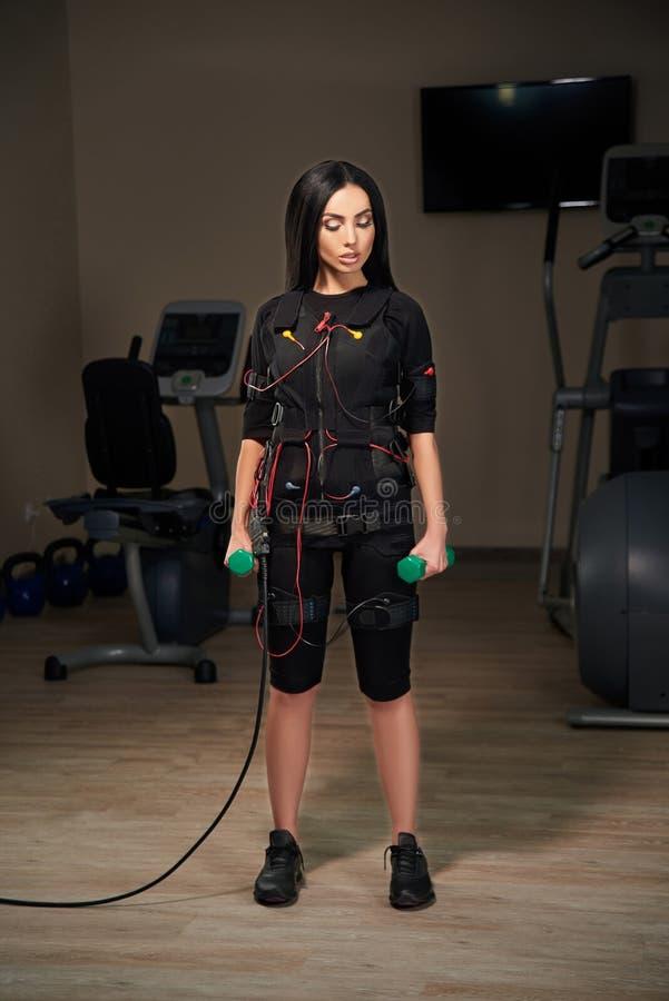 Muchacha morena en el traje del ccsme que se coloca con pesas de gimnasia efecto del resplandor foto de archivo libre de regalías