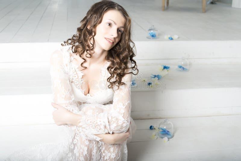 Muchacha morena en el vestido blanco que se sienta en las escaleras fotos de archivo