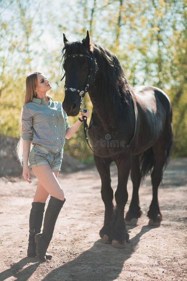 Muchacha morena hermosa con el pelo largo que presenta con un caballo rojo en bosque imagen de archivo libre de regalías