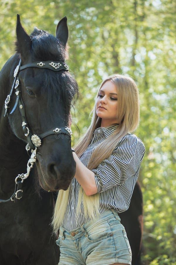 Muchacha morena hermosa con el pelo largo que presenta con un caballo rojo en bosque imágenes de archivo libres de regalías