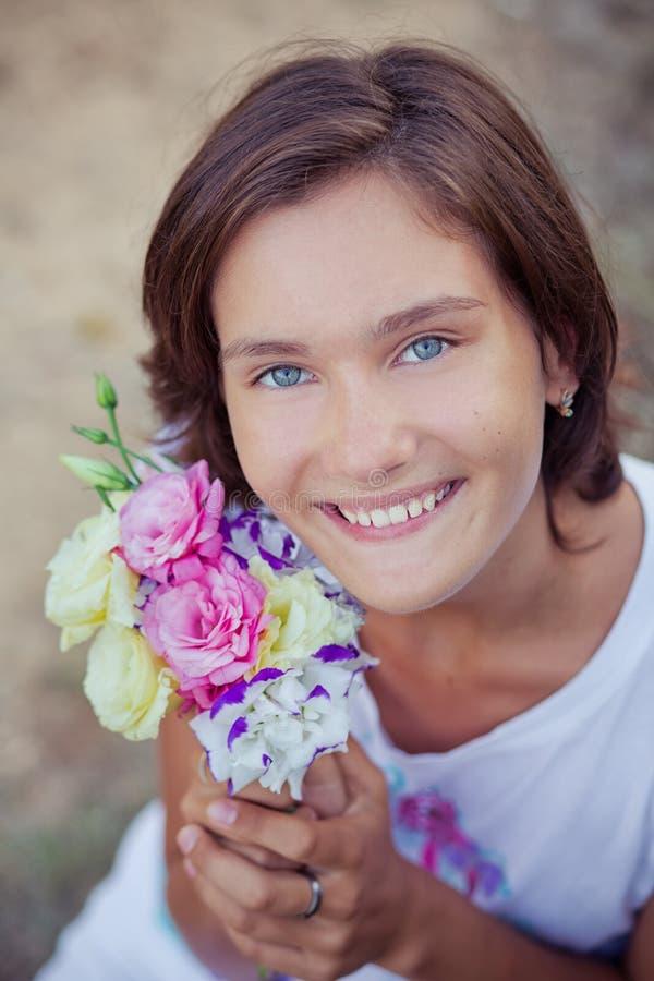 Muchacha morena hermosa con los ojos azules y el retrato de las flores fotografía de archivo libre de regalías