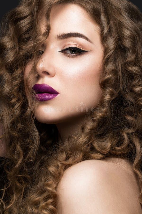 Muchacha morena hermosa con un pelo perfectamente rizado, y maquillaje clásico Cara de la belleza fotos de archivo