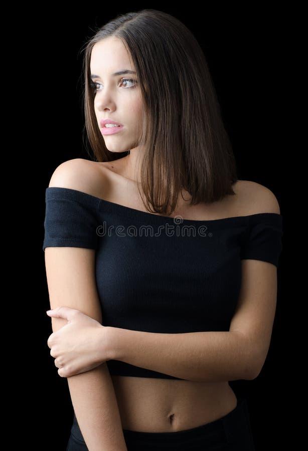 Muchacha morena hermosa en la ropa negra aislada en negro imagenes de archivo