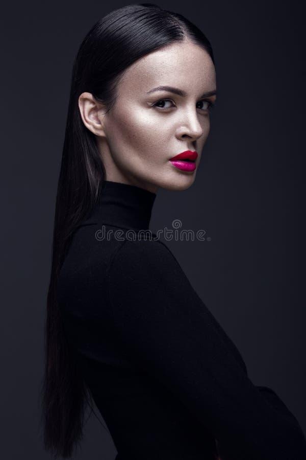 Muchacha morena hermosa en un vestido negro, un pelo recto y un maquillaje de moda Cara de la belleza del encanto fotos de archivo