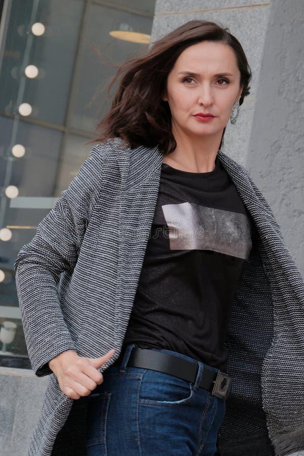 Muchacha morena hermosa en una capa y los vaqueros que presentan para una foto de moda en la calle Mujer en ropa del oto?o o de l imagen de archivo libre de regalías