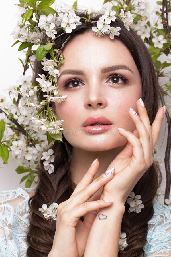 Muchacha morena hermosa en vestido azul con un maquillaje romántico apacible, labios rosados y flores La belleza de la cara imagenes de archivo