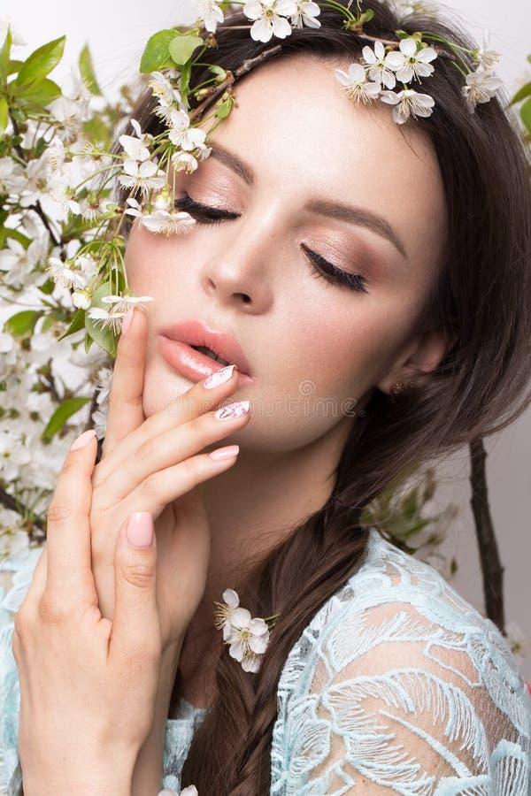 Muchacha morena hermosa en vestido azul con un maquillaje romántico apacible, labios rosados y flores La belleza de la cara fotografía de archivo