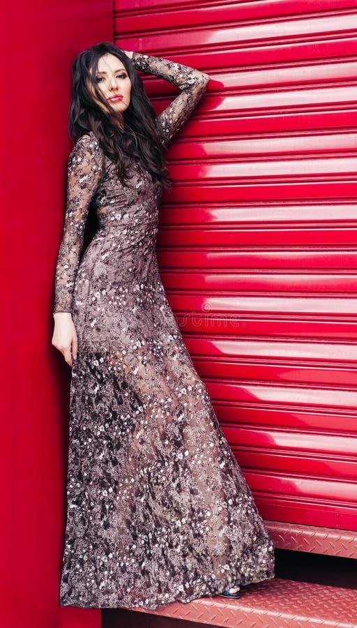 Muchacha morena hermosa que presenta con el pelo del vuelo en un vestido largo de moda en un fondo rojo Moda imagen de archivo