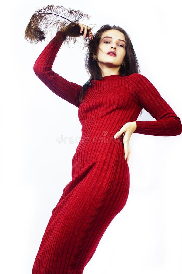 Muchacha morena joven de la moda de la señora en vestido rojo con la pluma, concepto elegante de la gente aislada en el fondo bla imágenes de archivo libres de regalías
