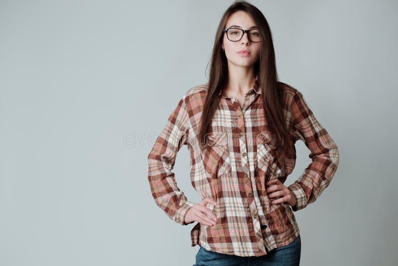 Muchacha morena joven linda segura de sí mismo en camisa y vidrios del control fotos de archivo