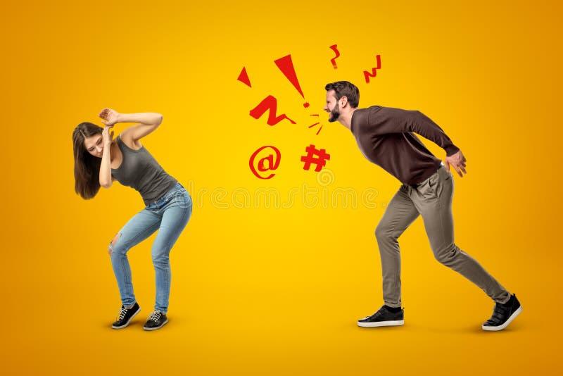 Muchacha morena joven que lleva vaqueros casuales y camiseta que se protege contra hombre de grito enojado en fondo amarillo fotografía de archivo