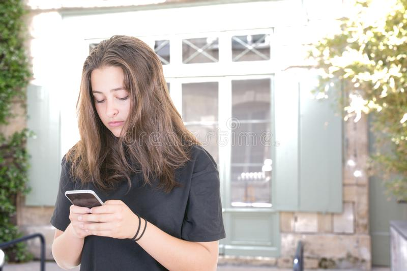 Muchacha morena joven que manda un SMS en smartphone en calle europea imagen de archivo