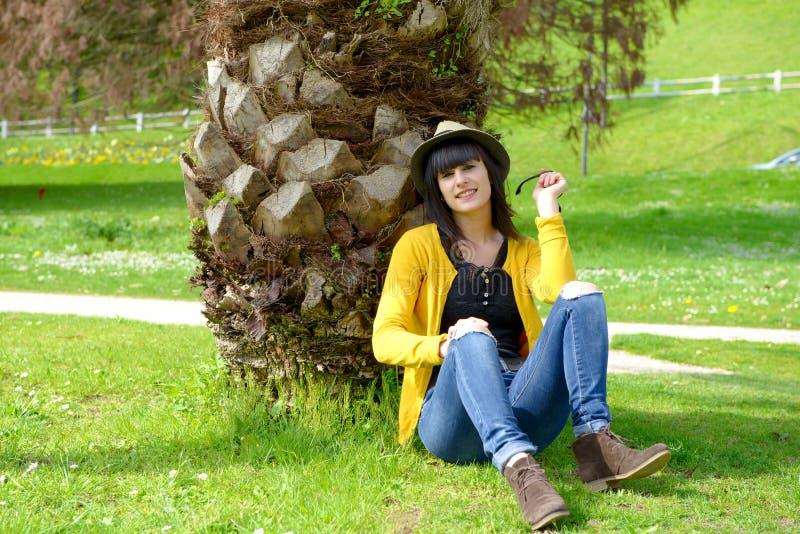 Muchacha morena joven que se sienta en hierba en parque al aire libre imagen de archivo