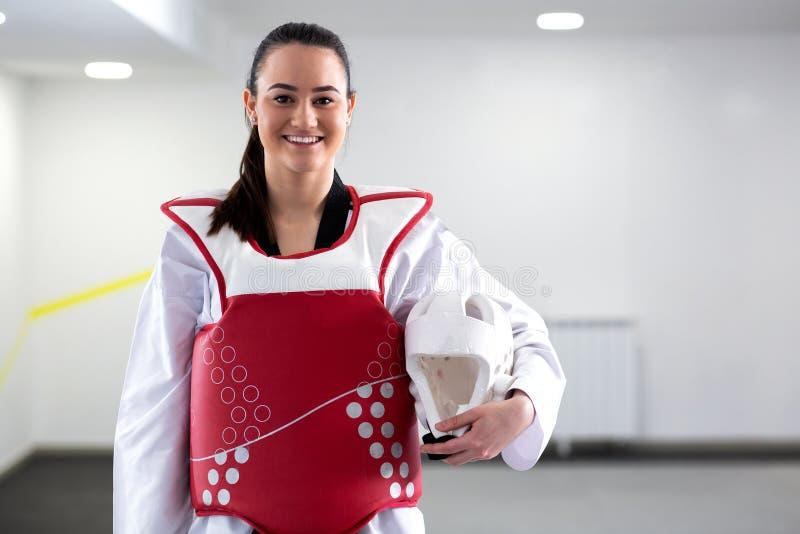 Muchacha morena linda joven que lleva el engranaje protector del arte marcial para el Taekwondo imagen de archivo
