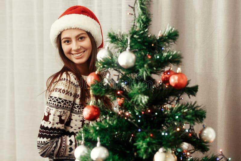 Muchacha morena magnífica en el sombrero rojo de Papá Noel y el reno acogedor fotos de archivo