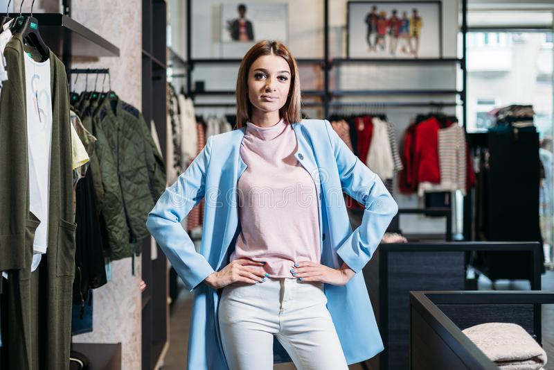 Muchacha morena modelo en la ropa elegante, presentando en tienda de ropa, una nueva tendencia de la ropa Bandera para una tienda foto de archivo