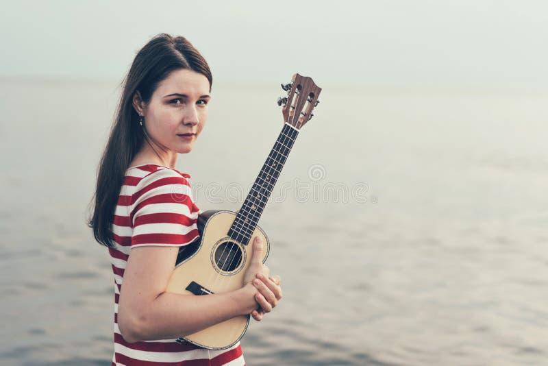 Muchacha morena por el mar con un ukelele acústico de la guitarra hawaiana fotos de archivo libres de regalías