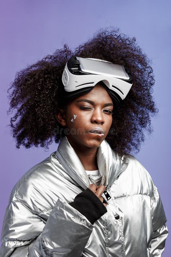 Muchacha morena rizada moderna vestida en una chaqueta plata-coloreada que lleva en su cabeza que los vidrios de la realidad virt fotografía de archivo