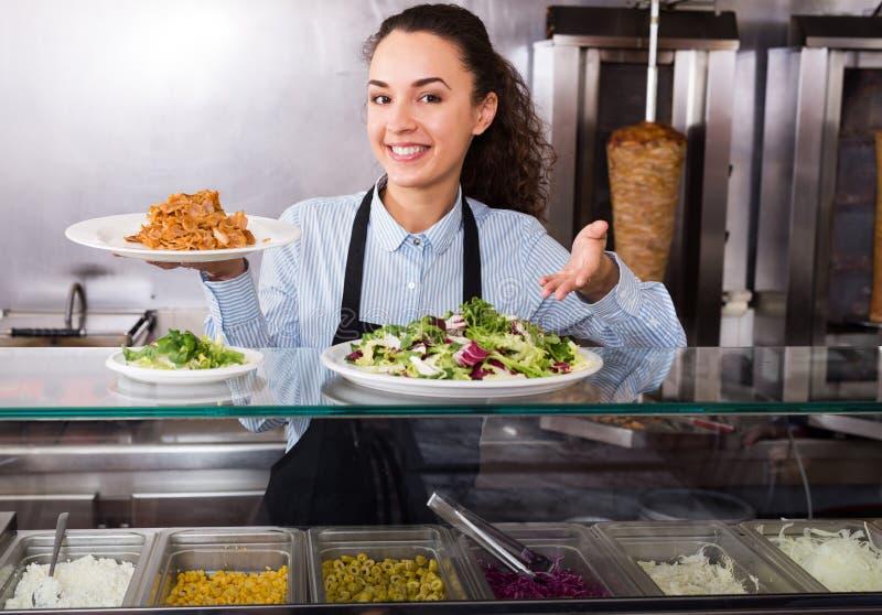 Muchacha morena sonriente con kebab y las verduras foto de archivo