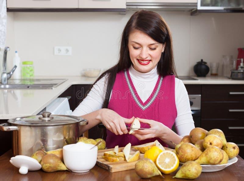 Muchacha morena sonriente que cocina el atasco de la pera fotografía de archivo