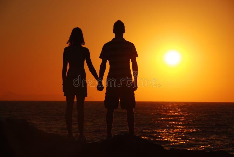 Muchacha, muchacho, mar y puesta del sol fotos de archivo