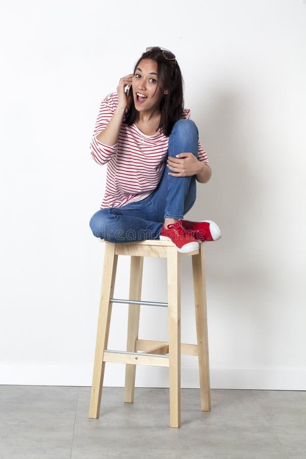 Muchacha multi-étnica sorprendente 20s que ríe en su teléfono celular imágenes de archivo libres de regalías