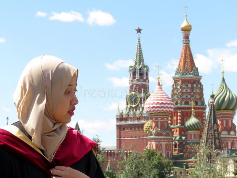 Muchacha musulmán en hijab en el fondo de la Moscú el Kremlin y de la catedral de la albahaca del St fotografía de archivo