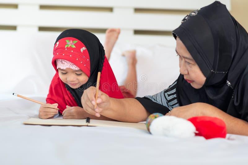Muchacha musulmán joven que escribe un libro con la abuela, niño islámico para hacer la preparación en casa imagenes de archivo