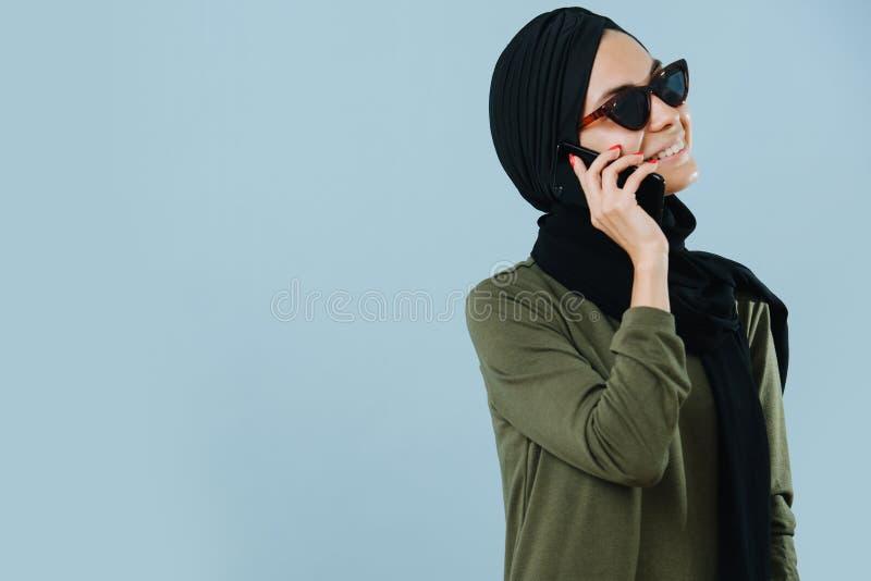 Muchacha musulmán sonriente joven que habla en el teléfono imagenes de archivo