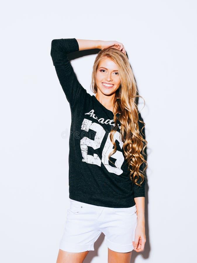 Muchacha muy hermosa con el pelo rubio largo que presenta en un fondo blanco Ella aumentó su mano sobre su cabeza y sonrisa sweat fotos de archivo
