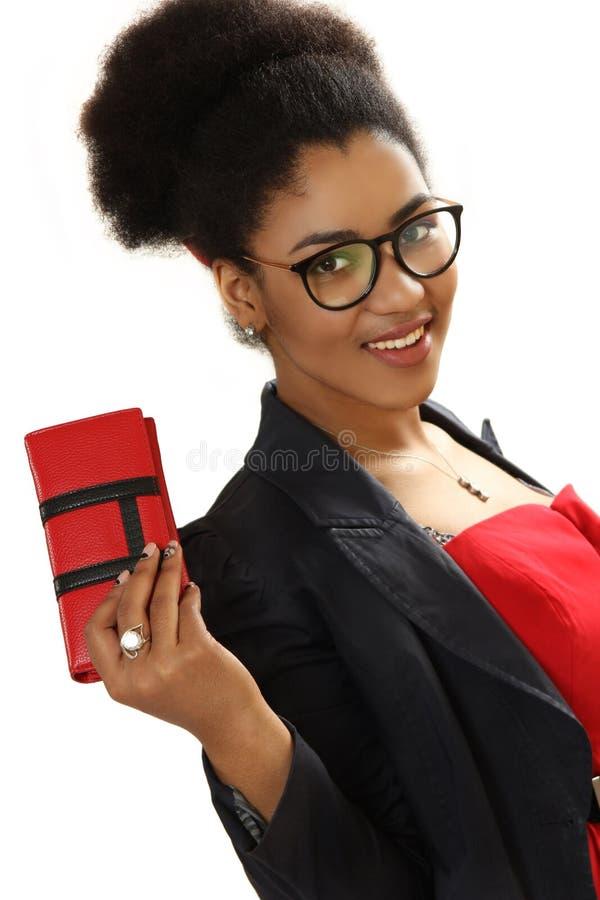 Muchacha negra agradable con un monedero en una mano fotografía de archivo