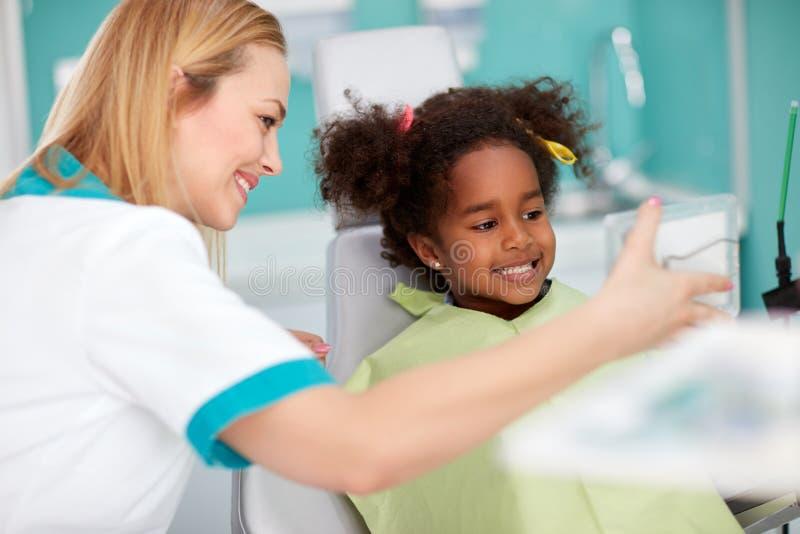 Muchacha negra agradable en la silla dental que muestra los dientes en espejo al denta imagen de archivo libre de regalías
