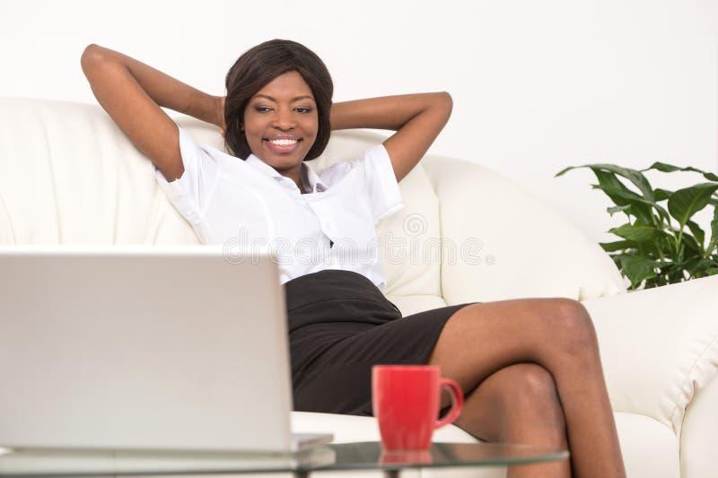 Muchacha negra joven con el ordenador portátil foto de archivo