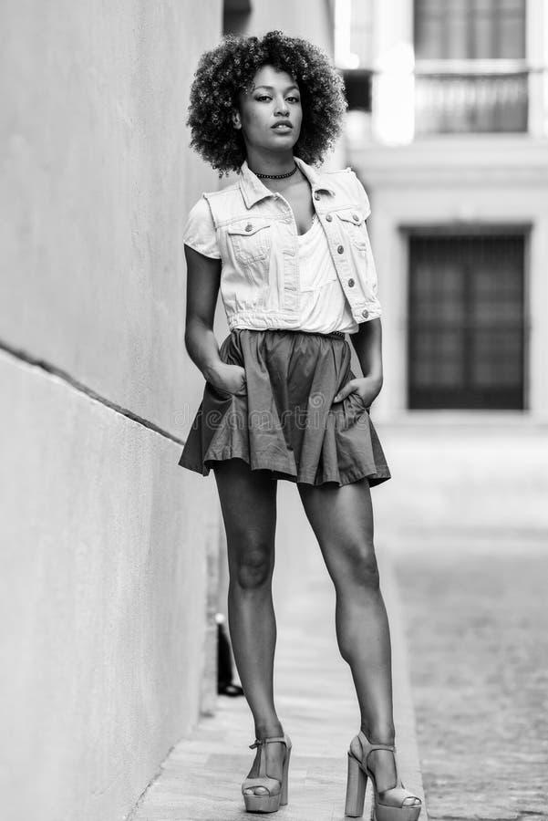 Muchacha negra joven, peinado afro, colocándose en fondo urbano foto de archivo libre de regalías