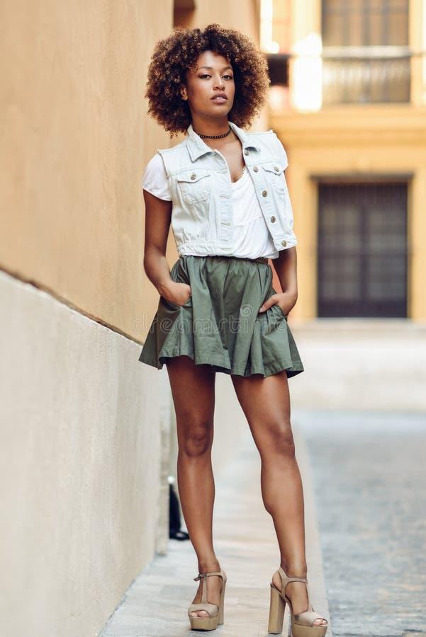 Muchacha negra joven, peinado afro, colocándose en fondo urbano fotografía de archivo libre de regalías