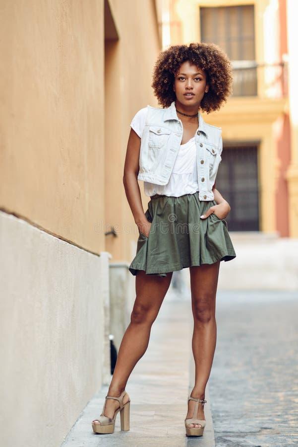 Muchacha negra joven, peinado afro, colocándose en fondo urbano fotos de archivo libres de regalías