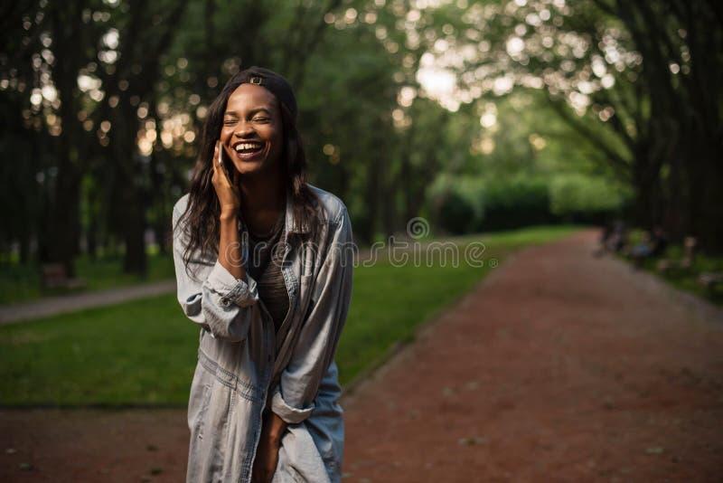 Muchacha negra joven y hermosa que habla en el teléfono y la risa Muchacha que lleva ropa casual y un casquillo fotos de archivo libres de regalías