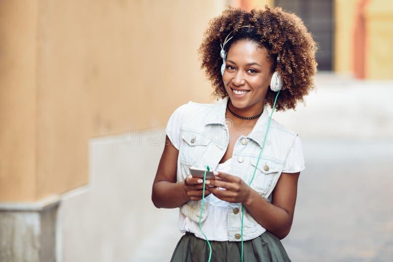 Muchacha negra, peinado afro, en calle urbana con los auriculares y fotografía de archivo libre de regalías