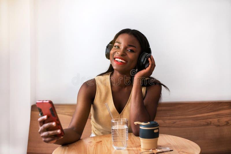 Muchacha negra sonriente que escucha la música en smartphone en el café fotografía de archivo