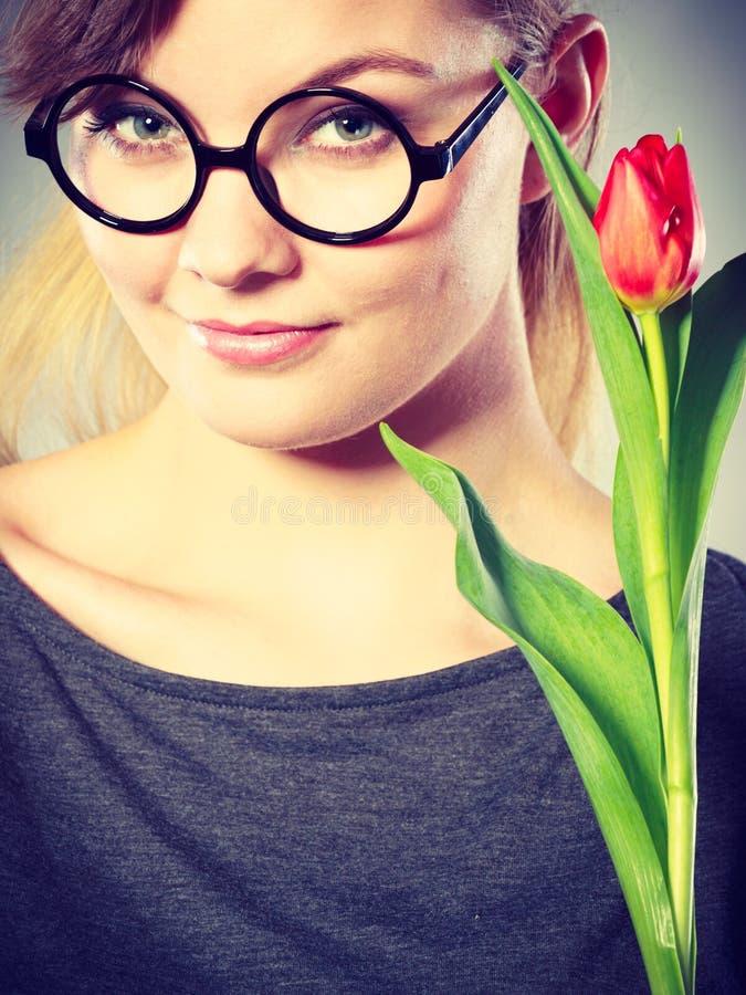 Muchacha nerdy de Seducive que sostiene el tulip?n fotografía de archivo libre de regalías