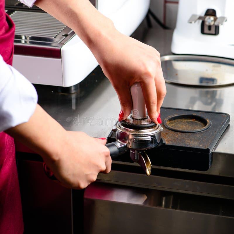Muchacha no identificada del barista que presiona el café molido con el genio internacional fotografía de archivo libre de regalías