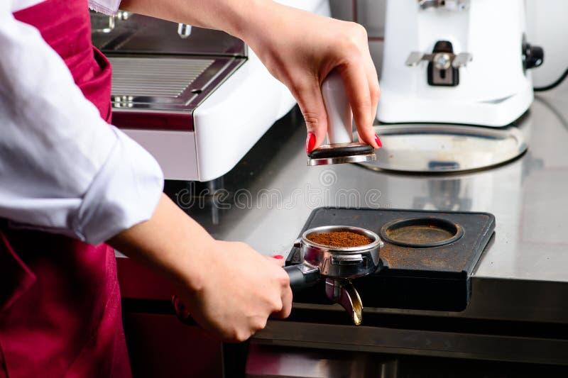 Muchacha no identificada del barista que presiona el café molido con el genio internacional fotos de archivo libres de regalías