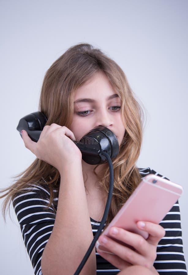 Muchacha ocupada que habla en el teléfono y en el smartphone foto de archivo
